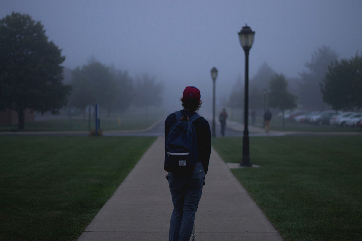 student walking in fog with backpack