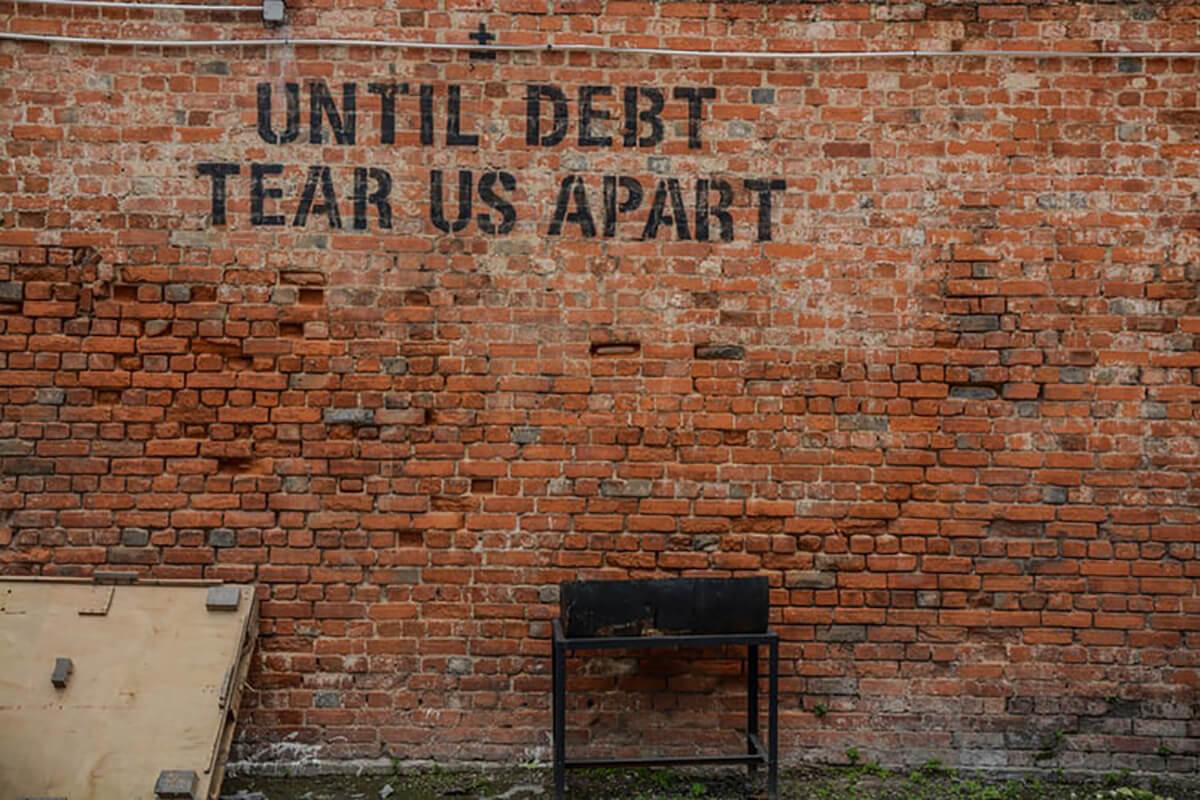 Until debt tear us apart sign