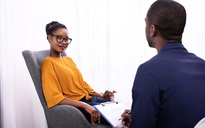 woman of color discussing with man of color while sitting in chairs