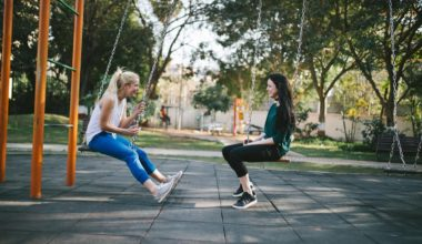 two girls sitting on swings facing each other