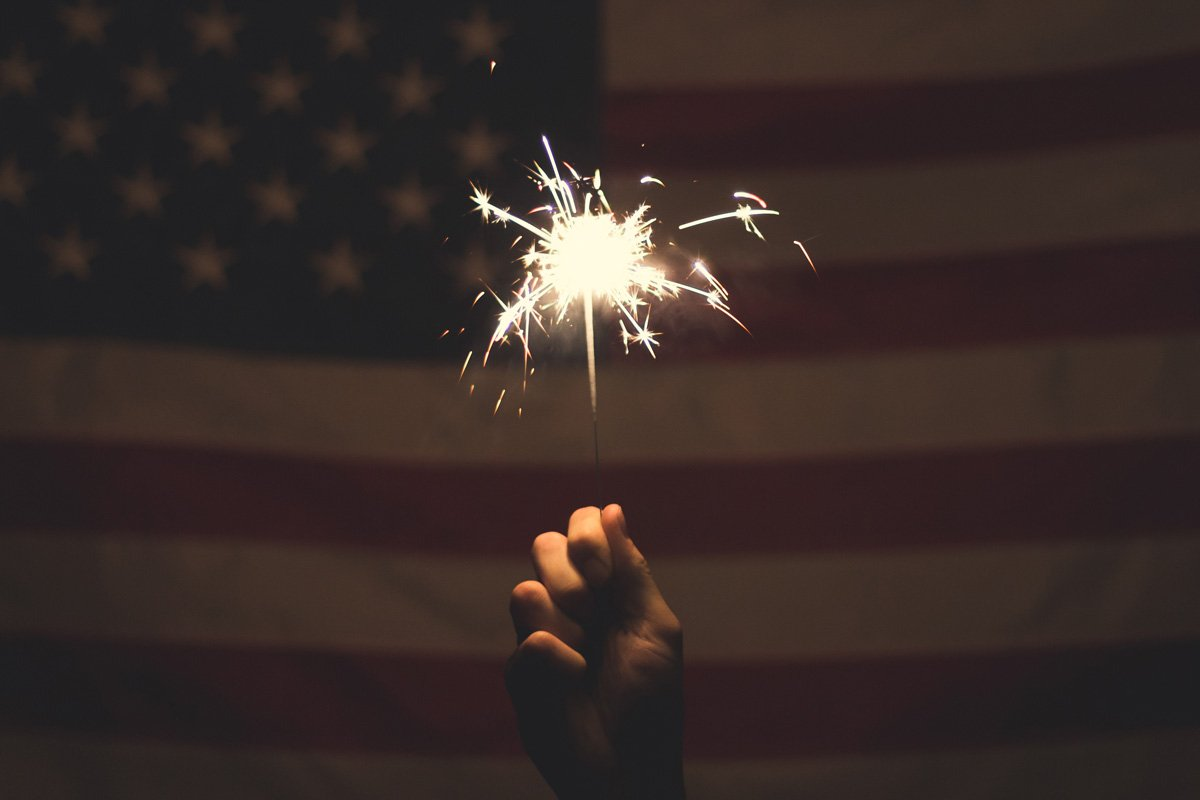 A hand holds up a sparkler firework in front of an American flag
