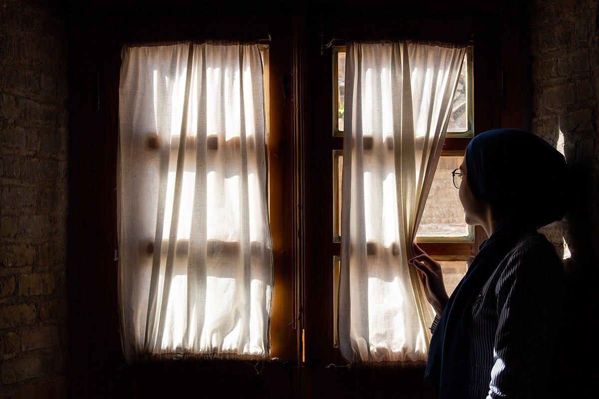 woman staring out of closed window