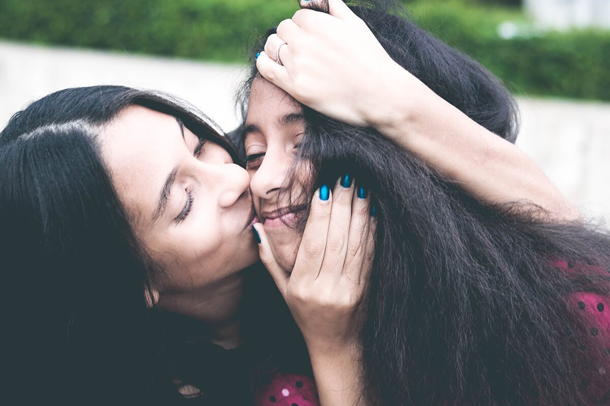 mother kissing daughter's face
