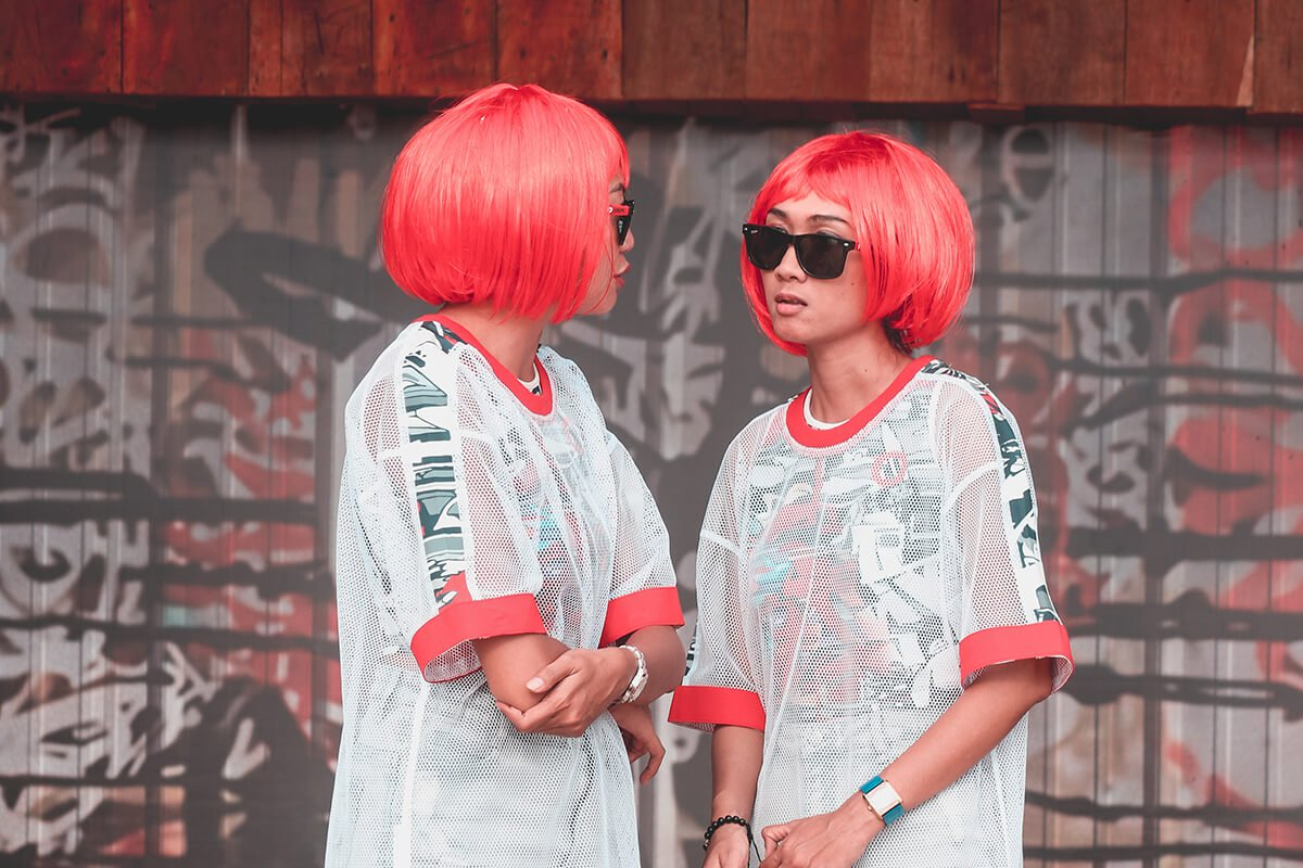 two girls in matching wigs looking at each other