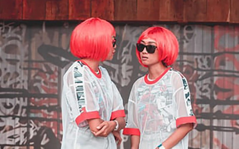 two young girls with matching wigs looking at each other