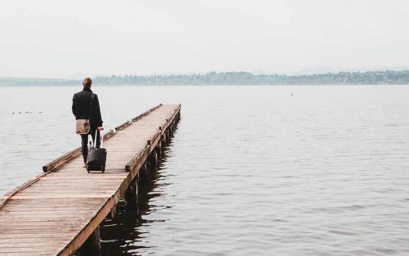 man walking down dock with suitcase