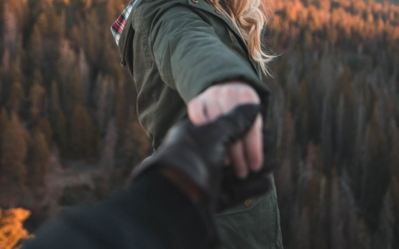 Woman holding a gloved man's hand on a mountaintop.