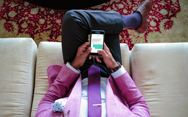 man sitting on couch texting Talkspace therapist