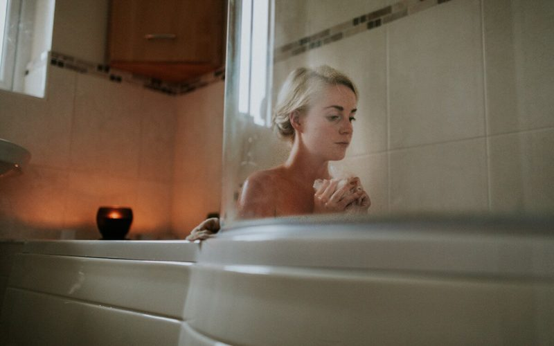 woman looking stressed in bathtub
