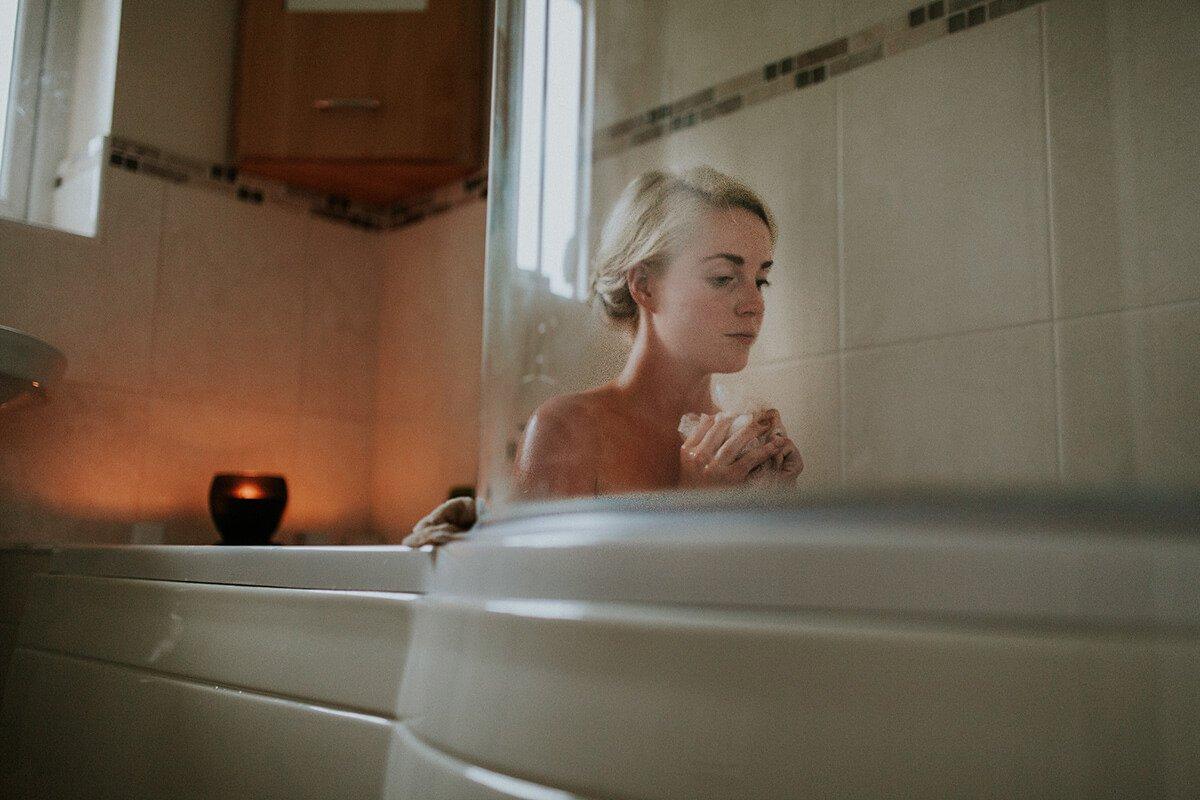 woman looking stressed in bathtub