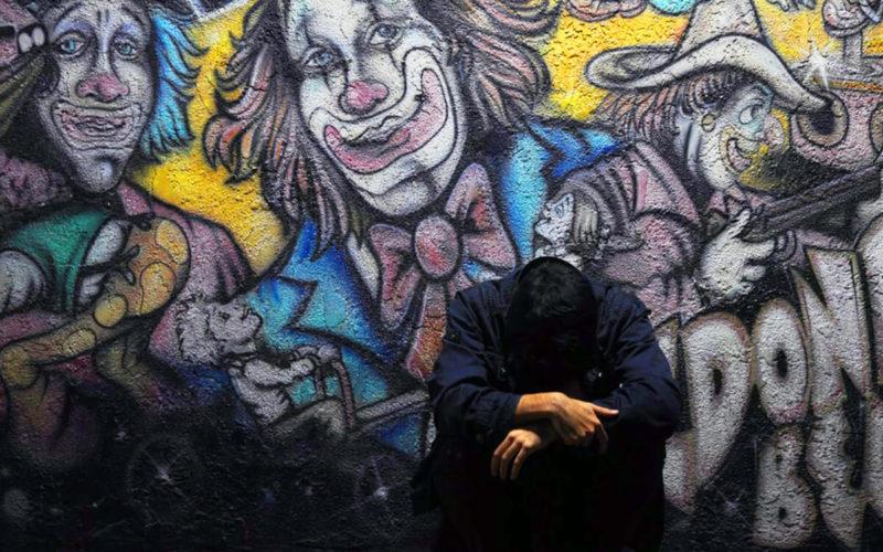 man looking down, clown graffiti behind him