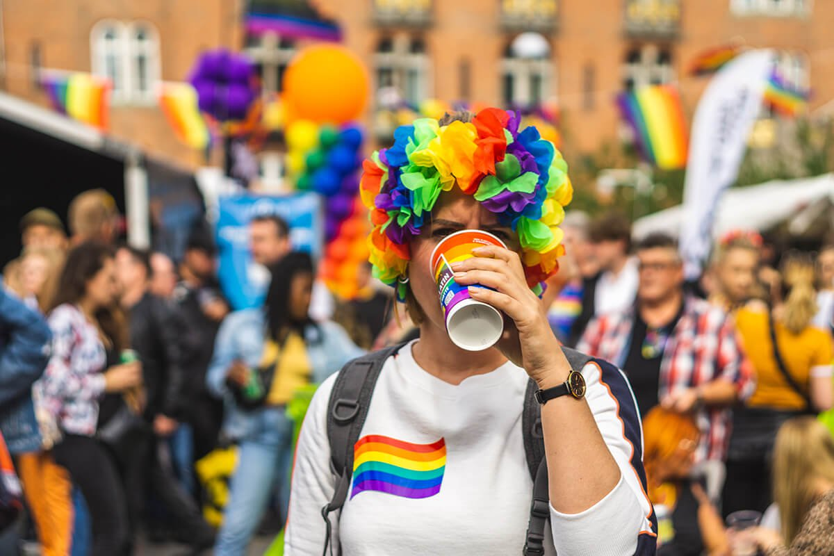 person dressed in pride colors drinking