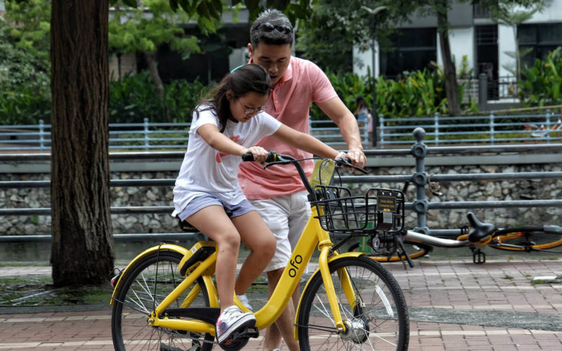 dad teaching daughter how to ride bike experiencing eustress or good stress