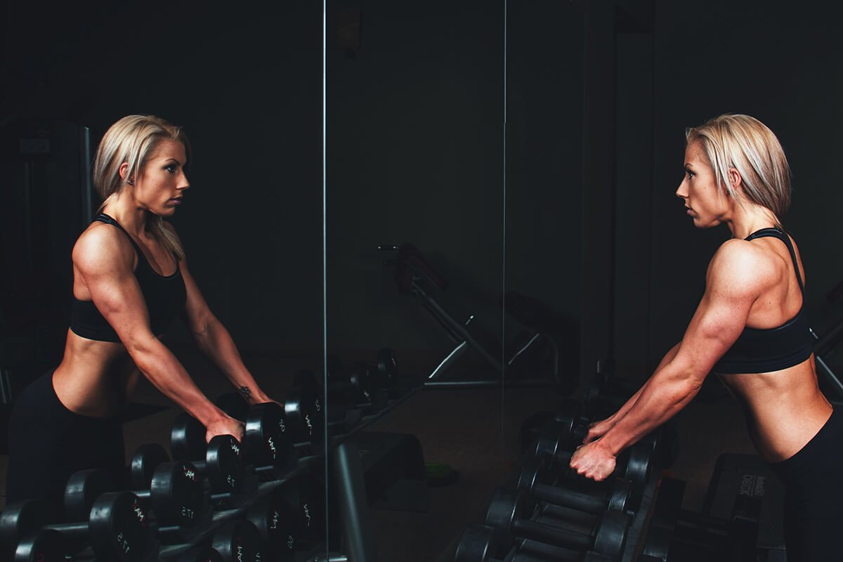 woman staring in mirror at gym holding weights, gym addiction