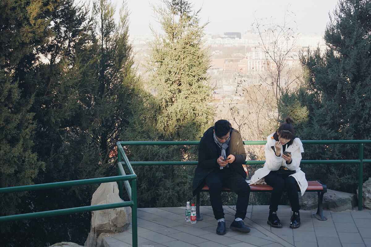 couple sitting on bench looking on phones