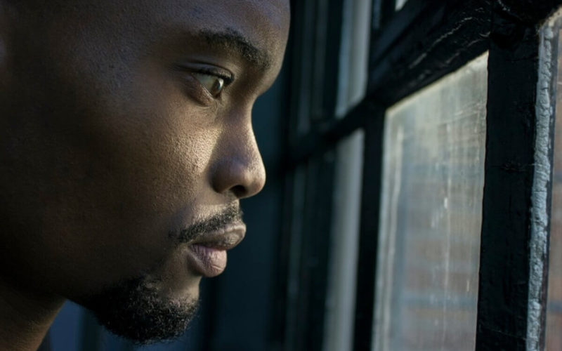 Man anxiously looking out of window.