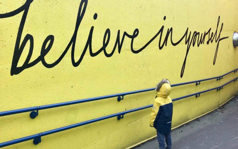 kid in raincoat looking at inspirational wall art