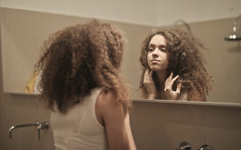 Woman looking at a mirror, body image