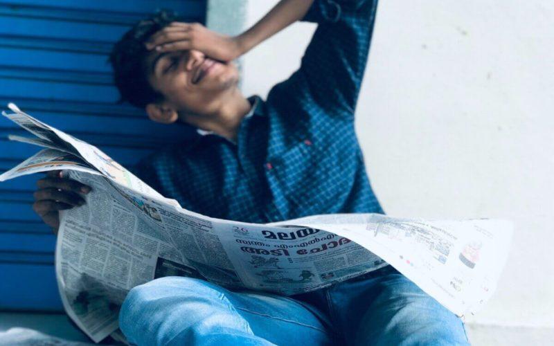 distressed man reading newspaper