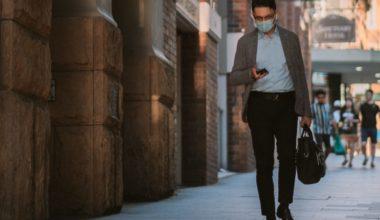 man walking down a street while texting