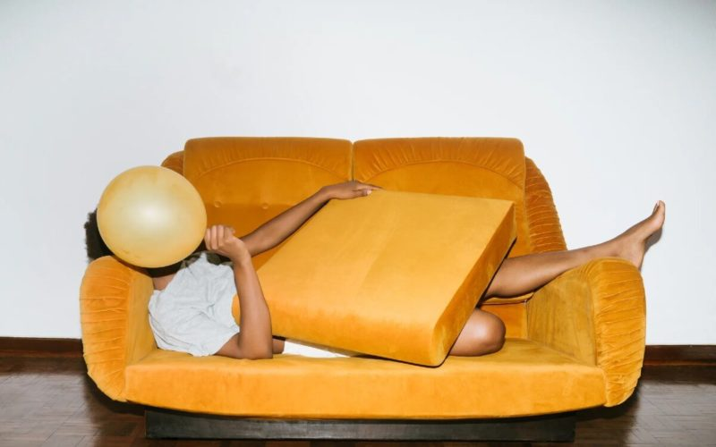 man lying on orange couch covering face with balloon