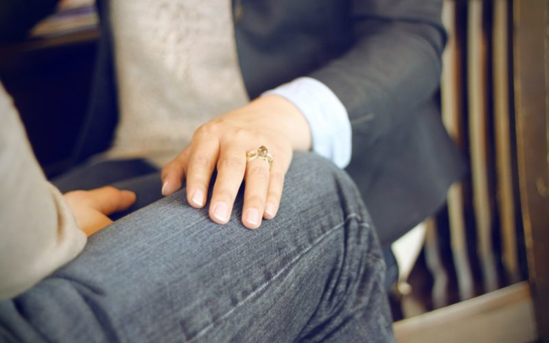 hand bearing a ring on someone's lap