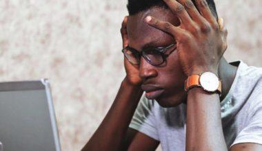 Man grabbing his head while looking at computer