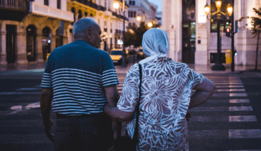 older couple holding hands crossing street