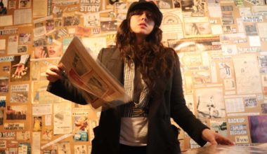 woman standing in a room covered in newspapers