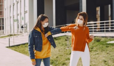 two women wearing masks and elbow bumping each other