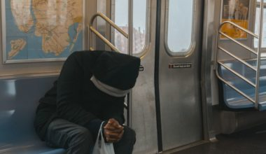 Man in black hoodie riding the subway