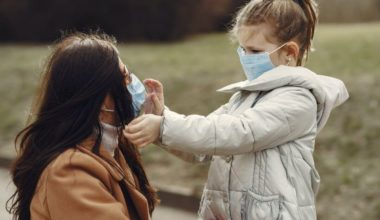 child fixing mask on mother's face