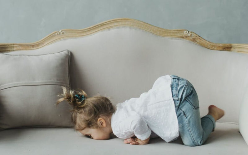 child lying face down on sofa
