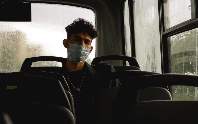 man wearing mask and sitting on bus