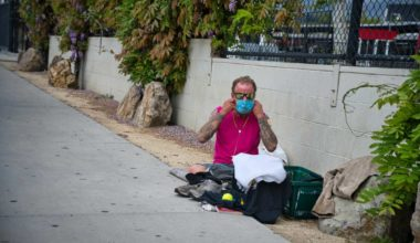 Homeless man wearing a mask on the street curb