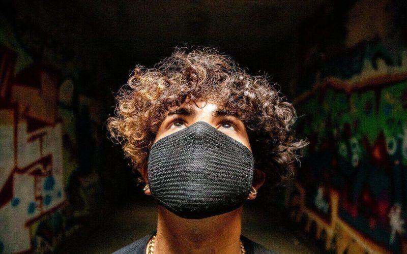 Man looking up wearing black mask