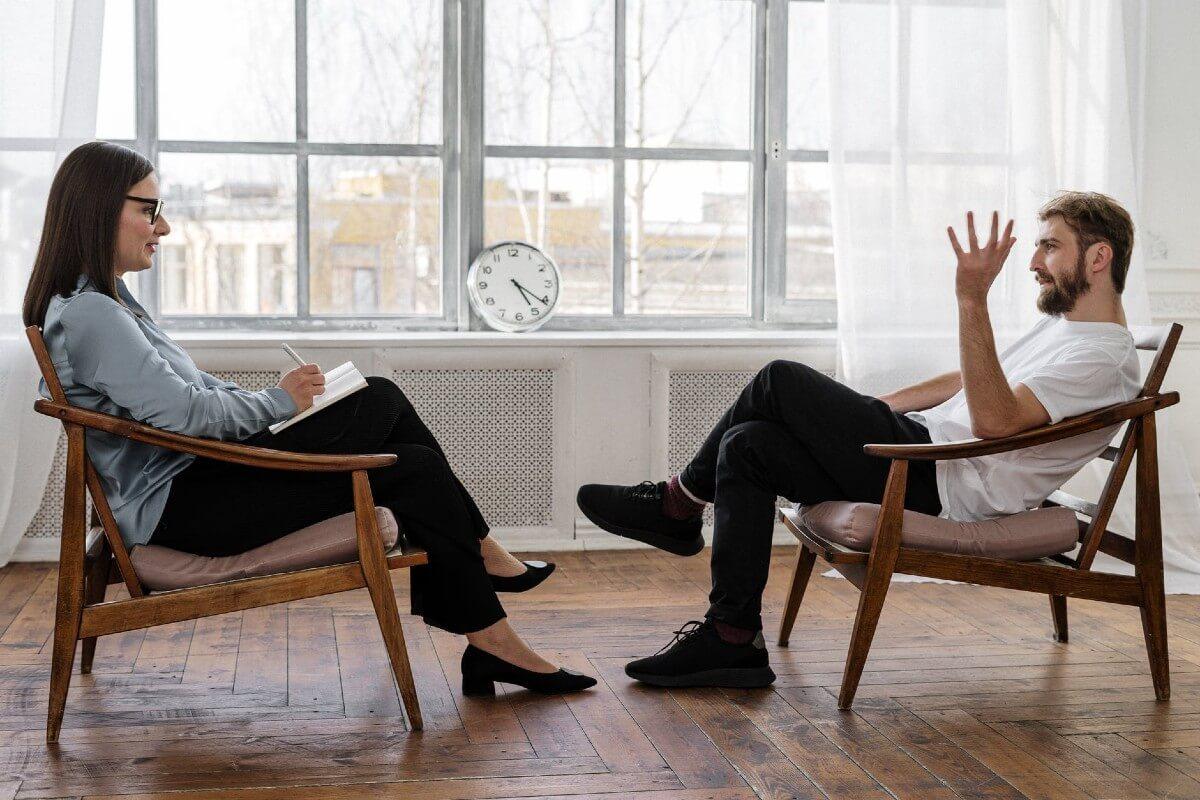 man speaking to female therapist