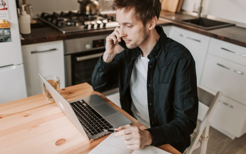 Man sitting with laptop making a phone call