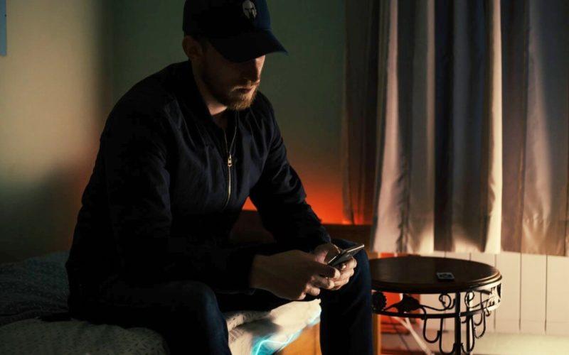 Man in dark room looking at his phone