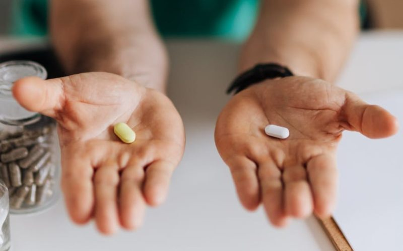 man holding two pills
