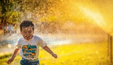 happy kid running through lawn sprinklers