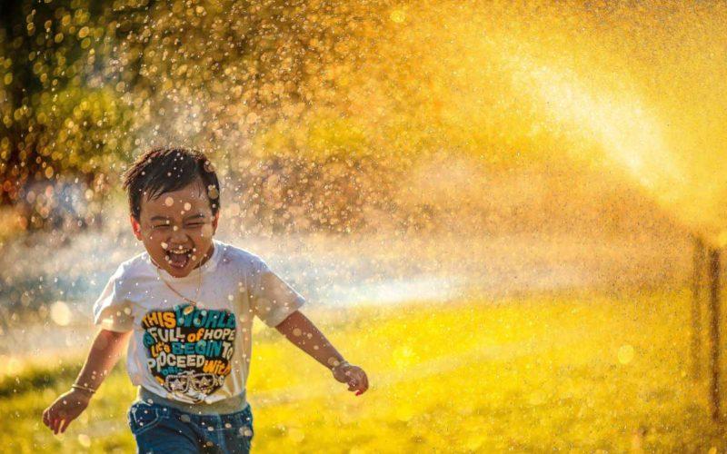 happy kid running through lawn sprinklers