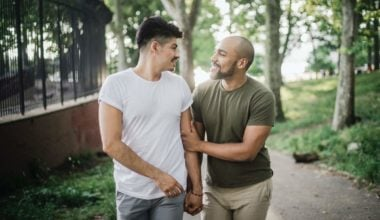 gay couple walking in the park holding hands
