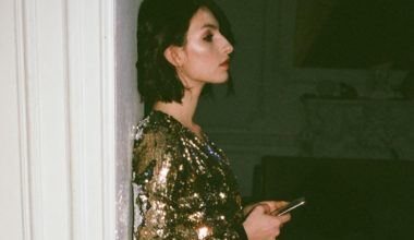 woman in gold dress leaning on doorframe