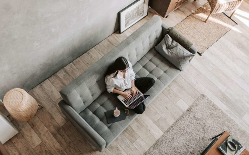 woman sitting on a couch with her computer and coffee