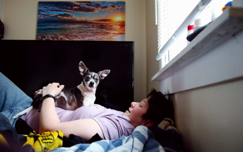 Depressed lady with a dog lying down on a mattress on the floor.