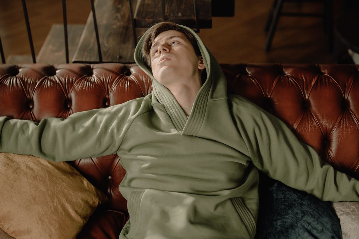 guy leaning back on sofa wearing a green hoodie