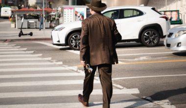 man walking across street
