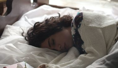 woman in sweater lying in bed exhausted