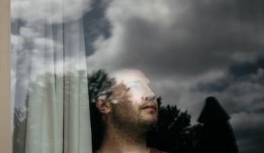 man looking out window